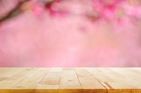 plain: Wood table top on blurred background of pink cherry blossom flower - can used for display or montage your products Stock Photo