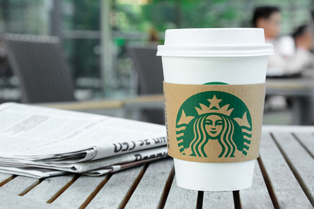 starbucks: Starbucks take away coffee cup with logo on sleeve, Starbucks brand is one of the most world famous coffeehouse chains from USA. Editorial