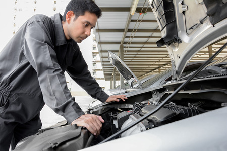Auto mechanic checking car engine at the garage - soft focus Stock Photo