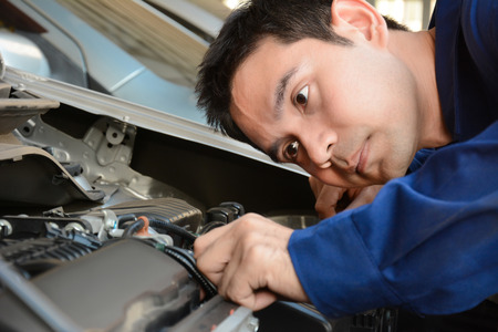 mecanico: Mec�nico auto que comprueba el motor de coche - cara enfocada