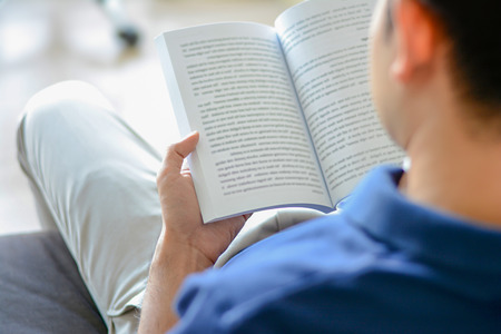 Young man reading book while sitting on the couch, over shoulder view with soft focus
