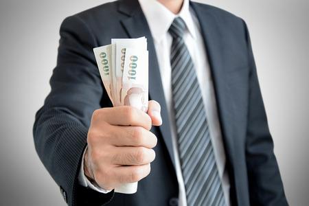 grasp: Businessman hand grabbing money, Thai Baht (THB) Stock Photo