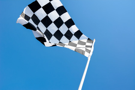 chequered: Checkered flag flying on blue sky background