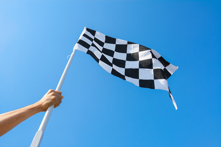 grabbing hand: Hand holding checkered flag on blue sky background Stock Photo