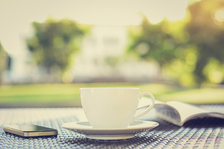 decaffeinated: Coffee cup with book  & smartphone on the table in blurred green nature background - vintage style colors, soft focus Stock Photo