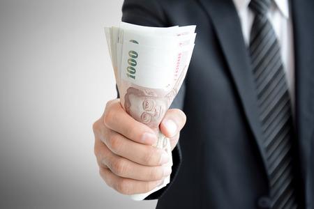 Businessman hand grabbing money, Thai Baht (THB) Stock Photo