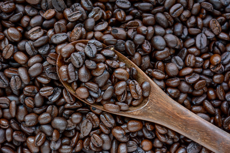 spoonful: Spoonful of coffee beans on coffee bean heap - soft focus