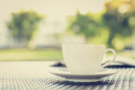 decaffeinated: Coffee cup with book on blurred green nature background - vintage tone