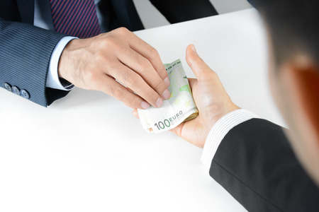 eur: Businessman hands giving & receiving money, Euro currency (EUR) - bribery concept
