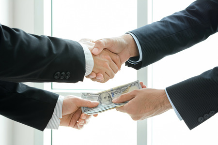 us money: Businessmen making handshake while passing money - dealing & bribery concepts