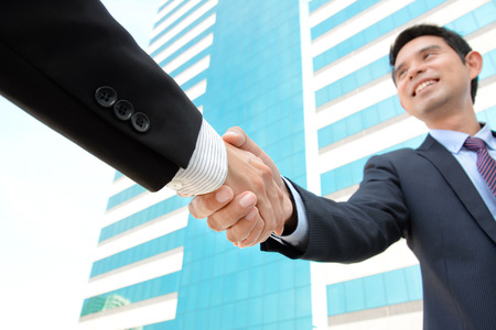 merger: Handshake of businessmen with smiling face - greeting , dealing, merger & acquisition concepts Stock Photo
