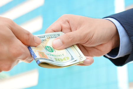 bribery: Hand receiving money, US dollars, from businessman - bribery concept Stock Photo