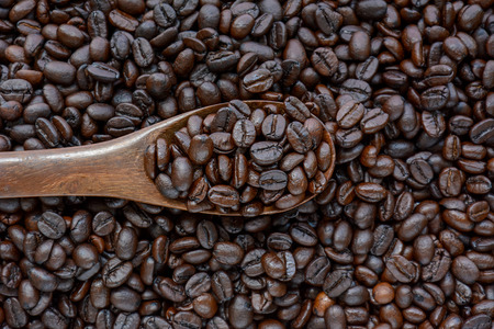 spoonful: Spoonful of coffee beans on coffee bean heap