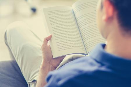 Mladý muž čtení knihy, zatímco sedí na gauči (přes rameno pohled) - vintage tón, soft focus Reklamní fotografie