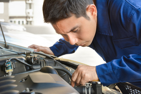 automotive repair: Auto mechanic checking car engine Stock Photo
