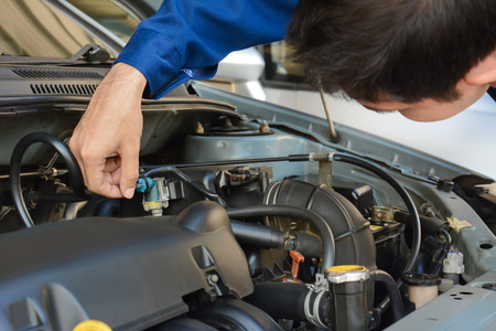 auto service: Auto mechanic checking car engine - soft focus