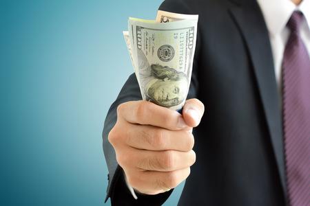 dinero: Empresario mano agarrando dinero, dólares (USD) facturas