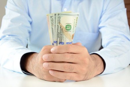 american banker: Hands holding money, US dollar (USD) bills, on the table