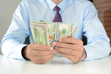 american banker: Businessman counting money,US dollar (USD) bills, on the table