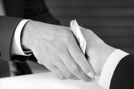 bribery: Handshake of businessmen with money, bribery concept - monochrome effect