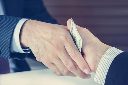 business deal: Handshake of businessmen with money, bribery concept - vintage tone