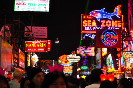 Pattaya, Thailand - Dec 31, 2013 : colorful neon signs of restaurants, pubs and bars with crowd walking on the street at Pattaya night walking street, Thailand