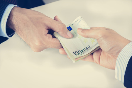 bribery: Businessman hands passing money, Euro currency (EUR), bribery concept - vintage tone