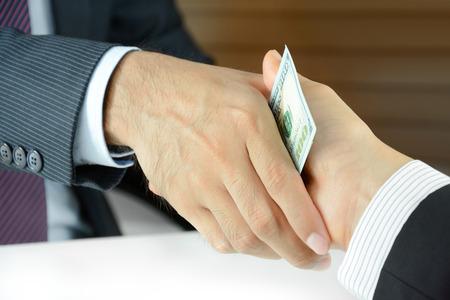 bribery: Handshake of businessmen with money - bribery concept