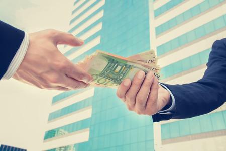 eur: Businessman hands passing money, Euro currency (EUR) - vintage tone