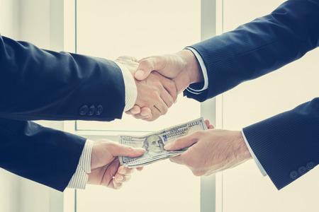 Businessmen making handshake while passing money, dealing & bribery concepts - vintage tone photo