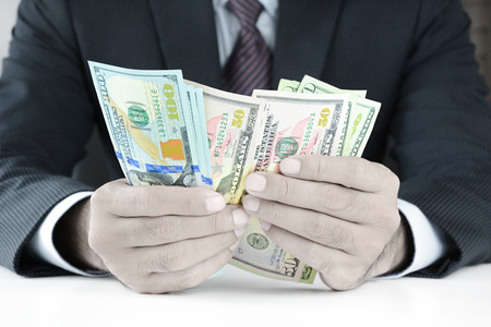 counting money: Businessman counting money,US dollar (USD) bills, on the table