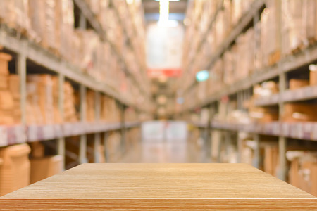 warehouse: Empty wood table top (or shelf) on blurred warehouse background - can montage or display your products Stock Photo