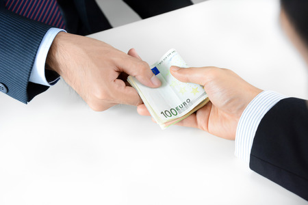 bribery: Businessman hands giving & receiving money, Euro currency (EUR) - bribery concept
