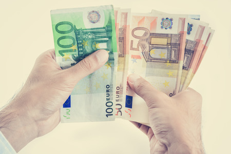 counting money: Hands counting money, Euro currency (EUR) - vintage tone