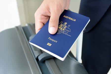 passport: Hands giving passport (of Australia) Stock Photo