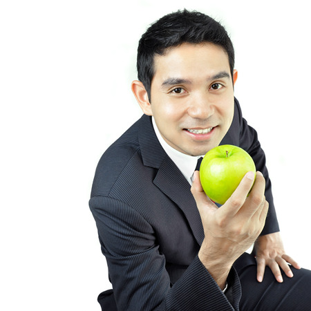 Young businessman holding green apple with smiling face photo