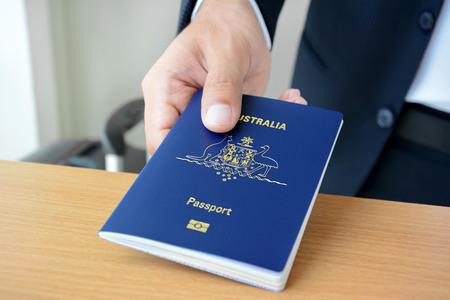 Hands giving passport (of Australia) Stock Photo