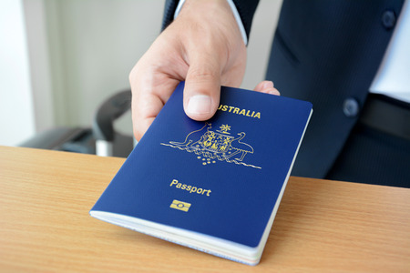 airport check in counter: Hands giving passport (of Australia) Stock Photo