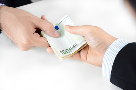 bribery: Businessman hands passing money, Euro currency (EUR) - bribery concept