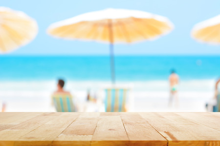 Holztischplatte auf verschwommen blauen Meer und weißen Sandstrand Hintergrund mit einigen Personen - für Montage oder verwendet werden, zeigen Sie Ihre Produkte Standard-Bild
