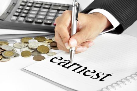 earnest: Mano con la pluma que se�ala a la s�plica ferviente palabra en el papel - conceptos financieros y de inversi�n Foto de archivo