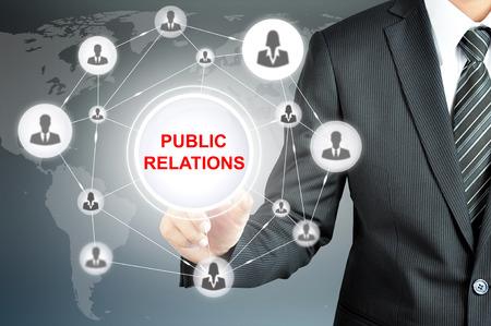 Homme d'affaires pointant vers RELATIONS PUBLIQUES signer avec les gens d'affaires icône réseau sur l'écran virtuel