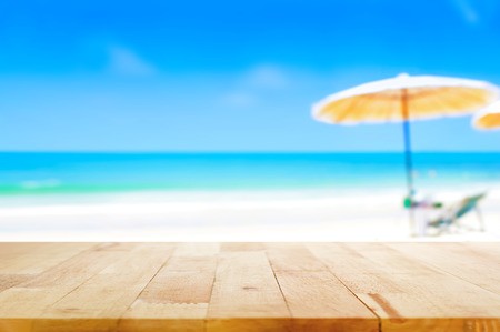 Wood table top on blurred blue sea and white sand beach background - can be used for display or montage your products Stock Photo