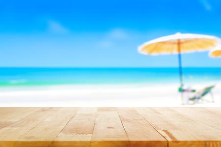 木桌上面在模糊的蓝色海和白色沙滩背景 - 可用于显示或蒙太奇您的产品