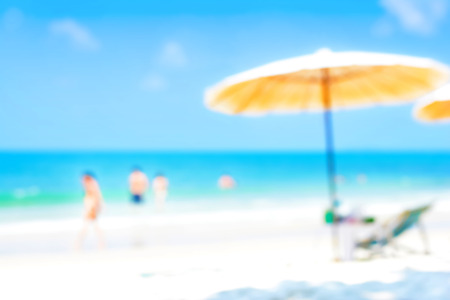 relaxation background: Blurred blue sea and white sand beach with parasol, beach chair and some people - holiday and vocation background concept Stock Photo