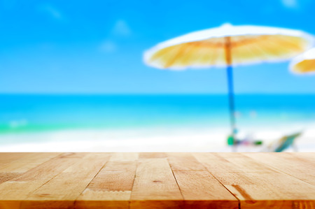 parasols: Wood table top on blurred blue sea and white sand beach background - can be used for display or montage your products Stock Photo