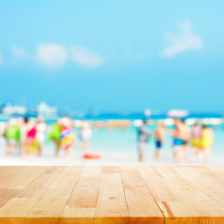 Wood table top with blurred people at the beach as background - can be used for display or montage your products