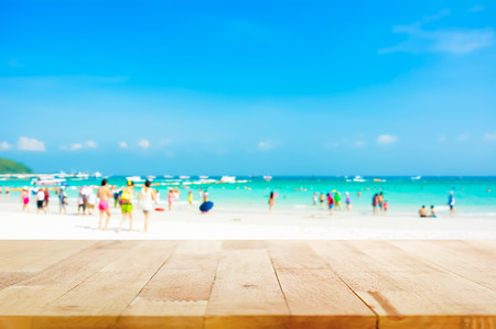 summer beach: Wood table top on blurred beach background with people in colorful clothes - can be used for display or montage your products
