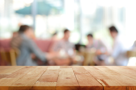 coffee shop: Wood table top with blurred people in cafe as background - can be used for montage or display your products