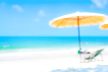 in the sand: Blurred blue sea and white sand beach with parasol and beach chair (with copy space) - summer background concept